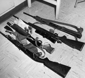 Rifles, first 3 on their sides, farthest one on the right is trigger side up