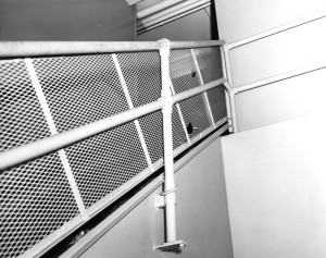 On the landing looking up at the mesh railing with two holes in it