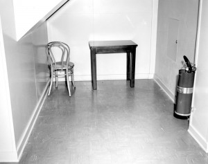 Corner of the room with chair, small table and fire extinguisher